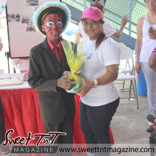 Spiderman boy and lady in Puma hat with gift basket special needs children Easter Bonnet parade at Queen's Park Cricket Club, color eggs, Sweet T&T, Sweet TnT, Trinidad and Tobago, Trini, vacation, travel