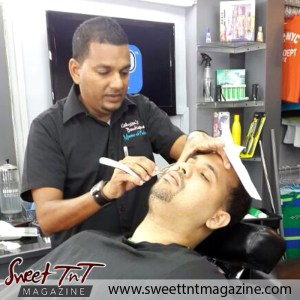Barber Faisal Mohammed, Master of Fades holds customer's face in salon, Sweet T&T, Sweet TnT, Trinidad and Tobago, Trini, vacation, travel