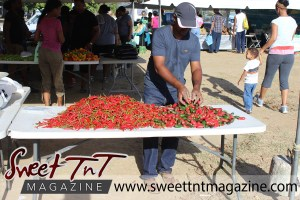 Man wearing blue jersey, blue jeans, blue cap, hat serving jalopeno peppers, pimento peppers, hot peppers, woman holding child walking, at Farmers' Market at Queen's Park Savannah, Port of Spain in parking lot in Sweet T&T, Sweet TnT, Trinidad and Tobago, Trini, vacation, travel