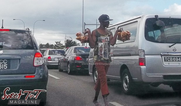 Limes vendor on the streets in between vehicles at red traffic light on highway in sweet T&T for Sweet TnT Magazine, Culturama Publishing Company, for news in Trinidad, in Port of Spain, Trinidad and Tobago, with positive how to photography.