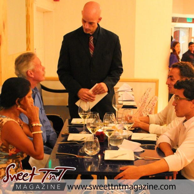 Craig Sells welcomes guests at their dinner table for Valentine's Day article in sweet T&T for Sweet TnT Magazine, Culturama Publishing Company, for news in Trinidad, in Port of Spain, Trinidad and Tobago, with positive how to photography.