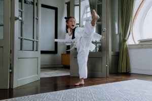 woman in white scrub suit standing on brown wooden parquet floor