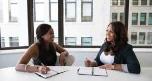 Interview questions to ask a potential employer, two woman in black sits on chair near table