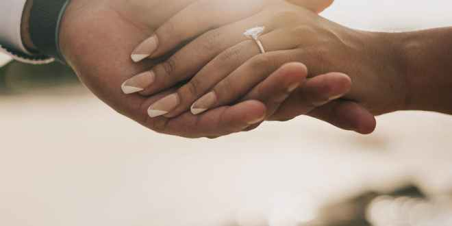 faceless couple holding hands with ring on sandy coast