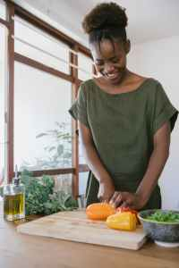 Boost immune system. Woman in green tank top holding orange bell pepper