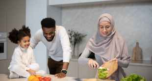 Standard of living, positive multiracial family cooking together in kitchen