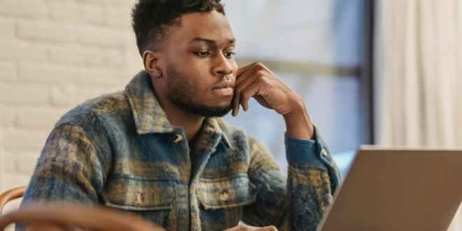 Remotasks. Serious black man working on laptop in workspace