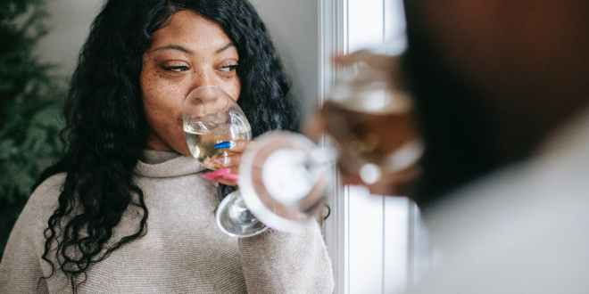 AUD. Dreamy black woman with anonymous boyfriend enjoying champagne in house