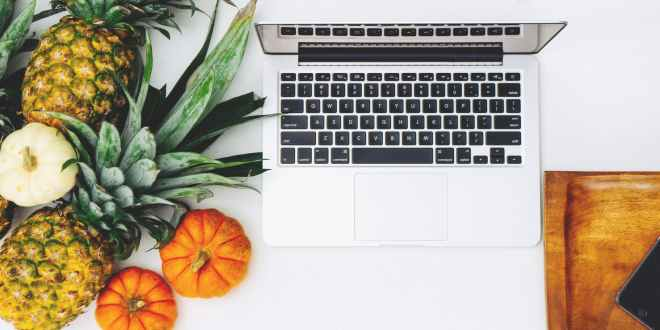 Food blog. White macbook near pineapple and pumpkin