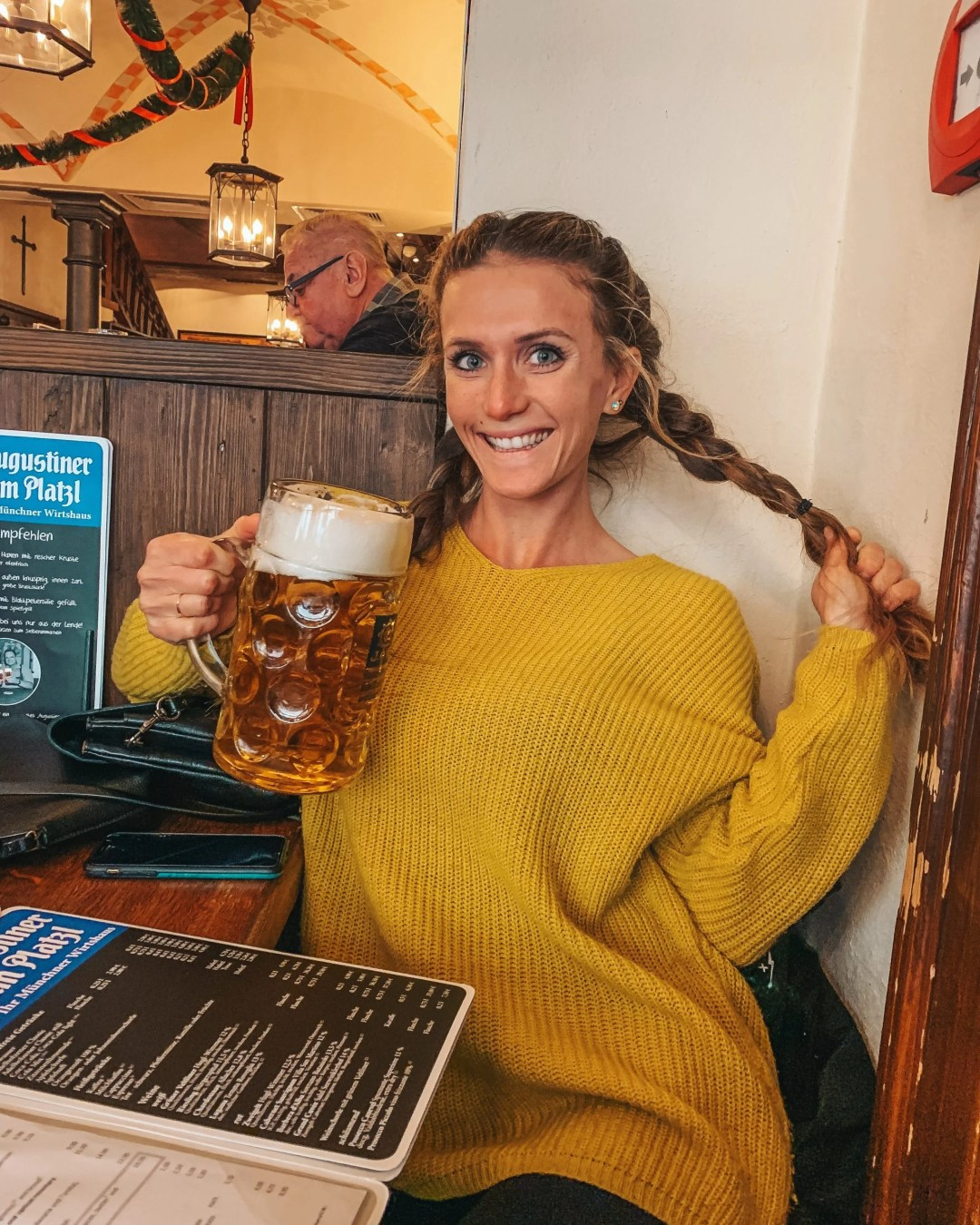 woman in yellow sweater holding large stein glass