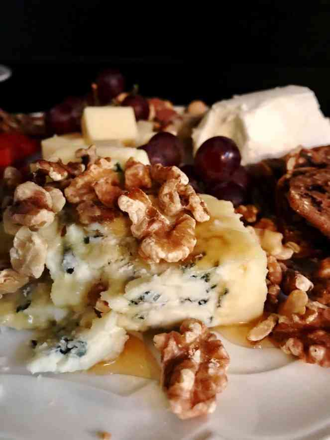 An elegantly simple cheese plate with blue cheese, honey, and walnuts.