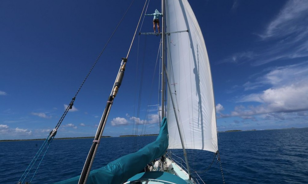Lea faithfully standing watch up the mast for coral heads in the uncharted lagoon waters.