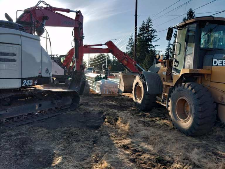 Two excavators working on a housing plat by moving drainage tubing and piping.