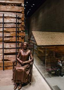 STATUE OF CLARA BROWN WITH SLAVE CABIN - After Brown was freed from slavery, she moved to Colorado, where she became an important community leader, helping other former slaves to settle there. The slave cabin to the right, from about 1853, had been on Edisto Island in South Carolina. (Credit: All Artifacts from the collection of the Smithsonian National Museum of African American History and Culture / Photo via New York Times)