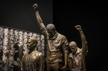 "BLACK POWER SALUTE, 1968 - Bronze statue symbolizing ""Black Power"" salute of Olympic sprinters Tommie Smith (2nd from l) and John Carlos (3rd from l), gold and bronze medal winners of the 200m race during 1968 Mexico City Olympics. The raised fist, a symbol of silent protest and black power for African American athletes, has been revived during the 2016 NFL season, begun by San Francisco 49'ers QB Colin Kaepernick. (Credit: All Artifacts from the collection of the Smithsonian National Museum of African American History and Culture / Photo by Jahi Chikwendiu / Washington Post)"