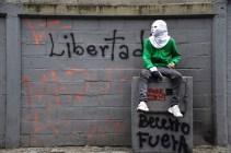 """A Venezuelan opposition activist sits against a wall reading """"Freedom!"""" during a protest against President Nicolas Maduro, in Caracas on May 8, 2017. (Photo: Juan Barreto / AFP / Getty)"""