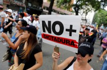 """Demonstrators rally during the so-called """"mother of all marches"""" against Venezuela's President Nicolas Maduro in Caracas, Venezuela, on April 19, 2017. (Photo: Marco Bello / Reuters) Demonstrators rally during the so-called """"mother of all marches"""" with a sign that reads """"No more dictatorship"""" against Venezuela's President Nicolas Maduro in Caracas on April 19, 2017. (Photo: Carlos Garcia Rawlins / Reuters)"""