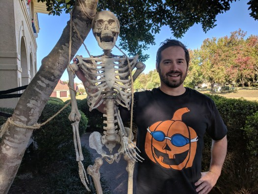Coach David with pumpkin goggles and a skeleton.