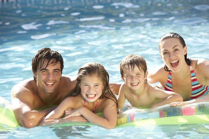 Young Family Relaxing In Swimming Pool Together