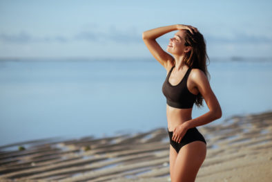 Outdoor shot of smiling young female model in bikini standing against blue sky.
