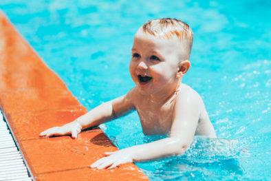 Portrait of happy little boy swimming in pool