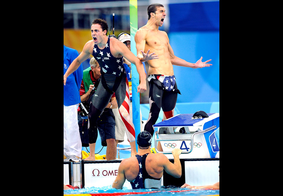 BEIJING, CHINA AUGUST 11TH, 2008--USA' Garrett Weber-Gale, left, and Michael Phelps celebrate with Jason Lezak, in the pool, the gold medal in the 4x100 Freestyle Relay at the 2008 Beijing Olympics.