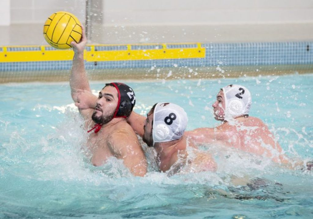 Oct 14, 2018; Baltimore, MD, USA; Monmouth Fighting Scots center Jesus Aguirre (21) fires a shot as Austin College 'Roos center Alex Rodriguez (8) and attacker Andrew Pope (2) apply pressure at the Newton White Athletic Center Natatorium. Greg Bartram/betterImage