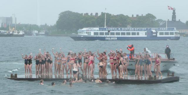 Frysende piger i bikini vinker fra en ponton bag den lille havfrue