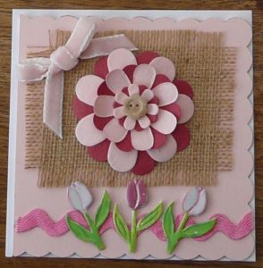 Pink card featuring raised central flower with individual petals and three raised tulips at the bottom of the picture.