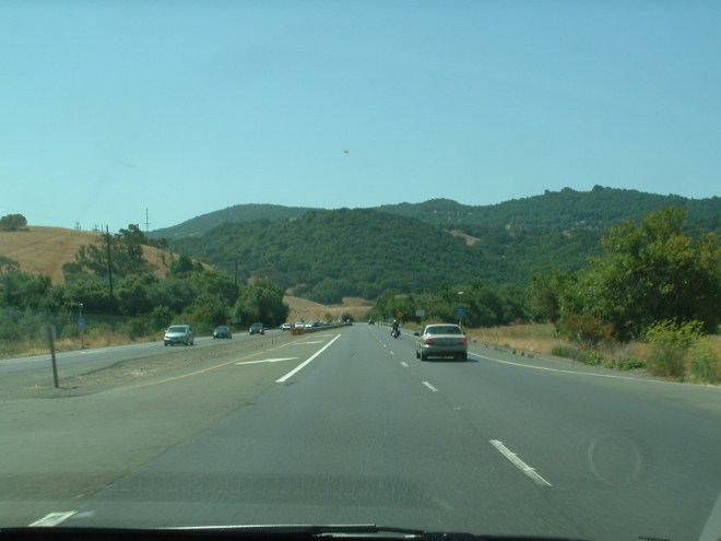 Photograph showing a driver's-eye-view of cars on a highway in rural California.