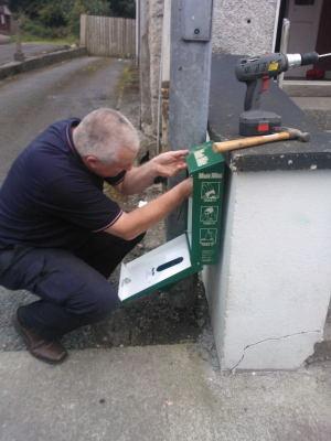 Mutt mitt dispenser being installed