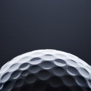 Partial golf ball against a dark backround