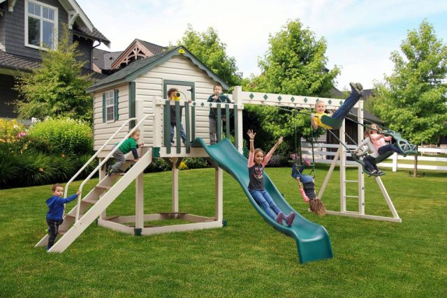 kids playing on a cabin playset