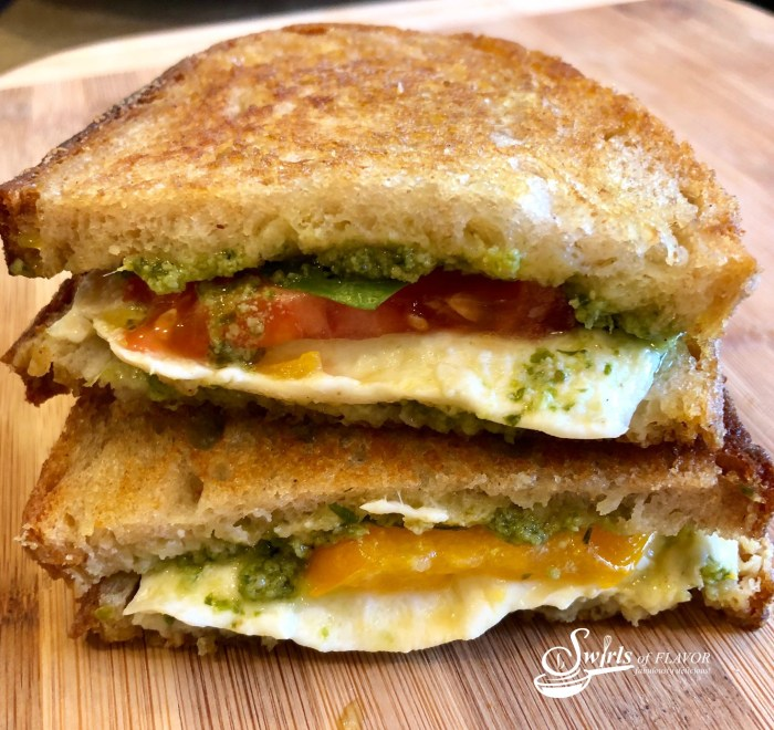 Caprese Grilled Cheese is bursting with fresh mozzarella, tomatoes, pesto, basil leaves, and of course, butter! A classic sandwich with an updated flavor! easy   grilled cheese   mozzarella   pesto   recipe   basil   tomatoes   #swirlsofflavor