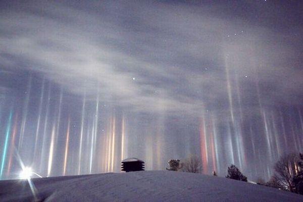 カナダの夜空に無数の「光の柱」が出現、ネオンや街灯に反射し色とりどりの光を放つ