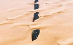 広大な砂漠に飲み込まれていく道路、自然の威力を示す空撮写真が美しい