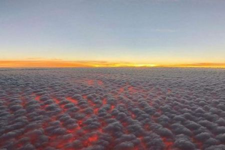 雲の下が燃えるような赤い光に染まる!ハワイ上空で撮影された景色が美しい