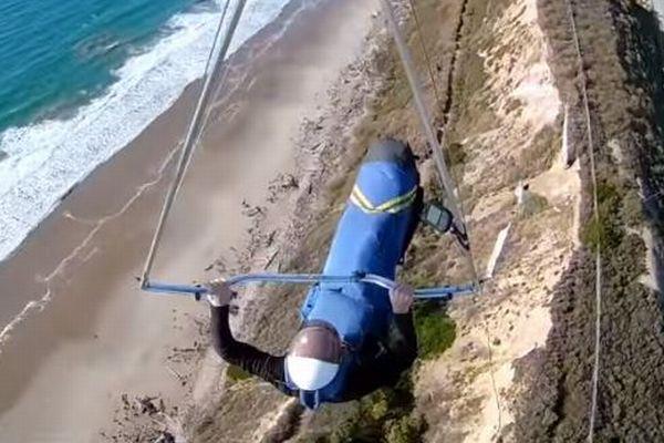 飛行中にハーネスが外れた!ハンググライダーの男性が必死にバーにぶら下がる