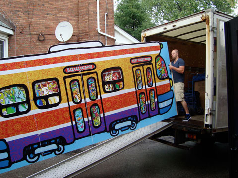 Loading the dismantled streetcar float into a moving truck.