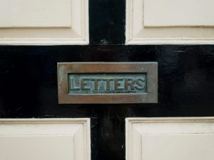Close up photo of a mail slot labeled letters