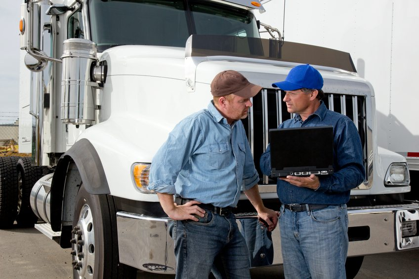 A royalty free image from the transportaion industry of two truck drivers using a laptop computer at a truckstop.