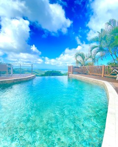 a blue pool with infinity edge and blue sky over Pic Paradis