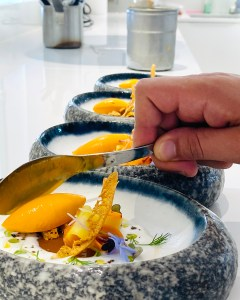 chef hand with spoon cuts into a bowl of food