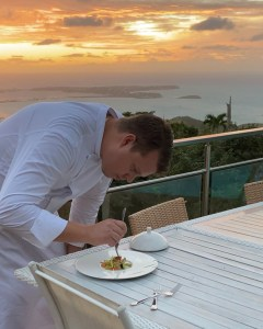 Chef at la villa hibiscus in st. martin preparing a dish with a sunset in the background