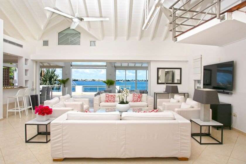 living room with a view of the water with white furniture