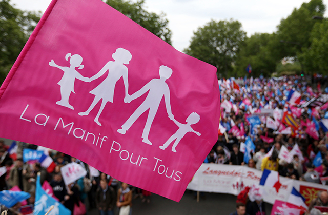 "A flag of the anti-gay marriage movement ""La Manif Pour Tous"" (Demonstration for all) is seen on the foreground while people demonstrate during a mass protest on May 26, 2013, in Paris against a gay marriage law. France on May 18 became the 14th country to legalise same-sex marriage after President Francois Hollande signed the measure into law following months of bitter debate and demonstrations. PLacard at centre reads ""Same-sex marriage, no"". AFP PHOTO THOMAS SAMSON"