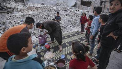 صورة على أنقاض بيوت مدمرة.. إمام يقدم إفطارا لأيتام في إدلب