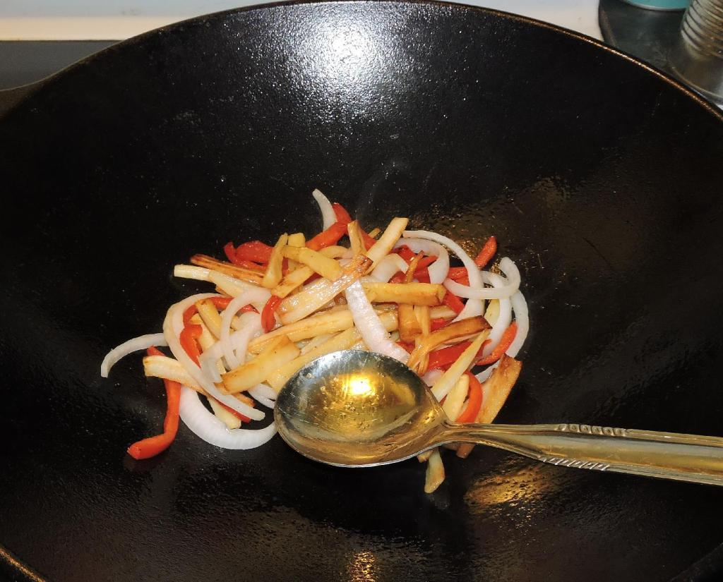 Parsnips, red pepper and onion being stir-fried together