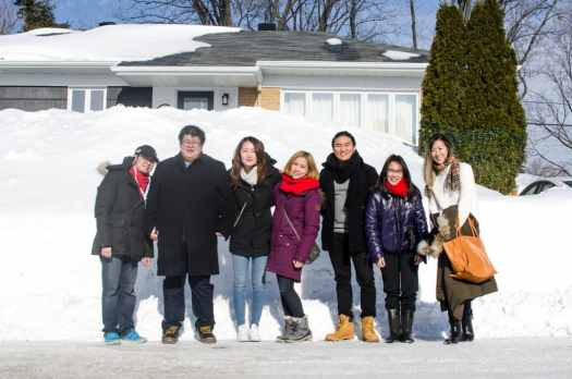 A group of 7 individuals pose in front of a snow bank that is almost as high as the Airbnb house itself.