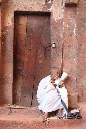 Hermit reads from his bible on the steps of a Lalibela church